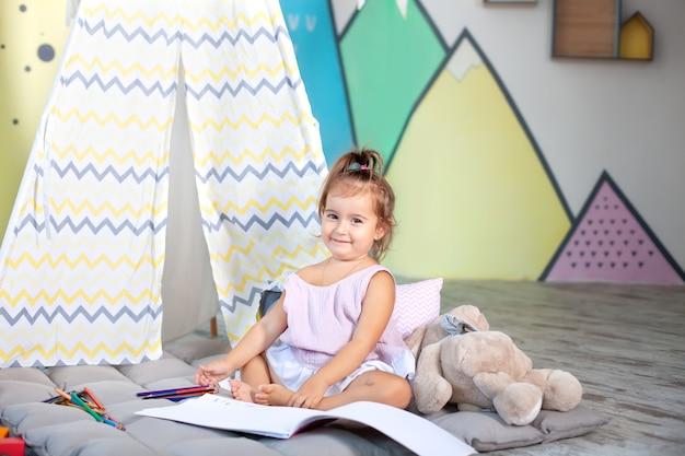 Smiling little caucasian girl draws with pencils in children room portrait  happy child