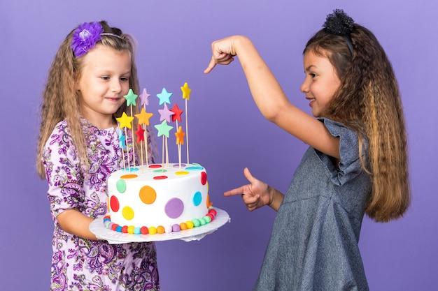 Улыбающаяся маленькая кавказская девочка, указывающая на довольную маленькую блондинку, держащую торт ко дню рождения, изолированную на фиолетовой стене с копией пространства