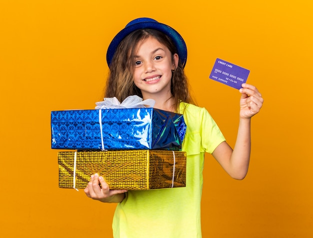 Smiling little caucasian girl with blue party hat holding credit card and gift boxes isolated on orange wall with copy space