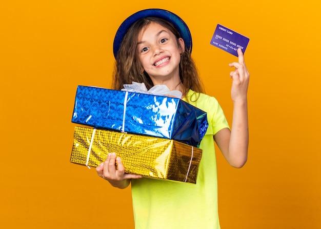 Улыбающаяся маленькая кавказская девушка в синей партийной шляпе, держащая подарочные коробки и кредитную карту, изолированную на оранжевой стене с копией пространства