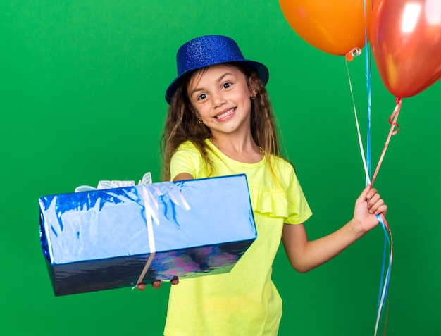 Smiling little caucasian girl with blue party hat holding helium balloons and blue gift box isolated on green wall with copy space