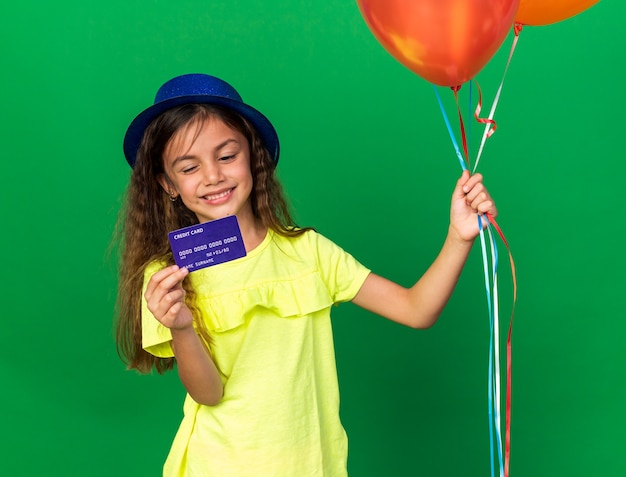 Smiling little caucasian girl with blue party hat holding helium balloons and looking at credit card isolated on green wall with copy space