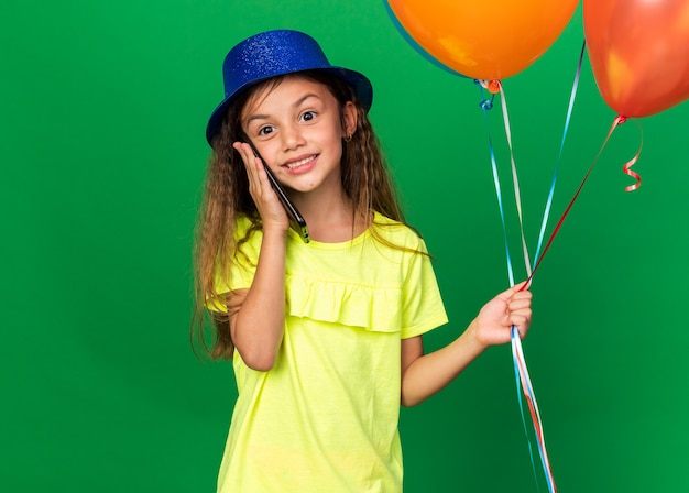 Smiling little caucasian girl with blue party hat holding helium balloons and talking on phone isolated on green wall with copy space
