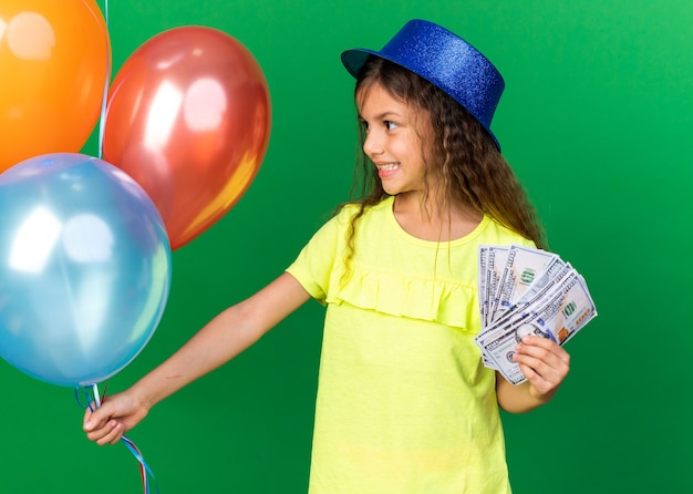 Smiling little caucasian girl with blue party hat holding money and looking at helium balloons isolated on green wall with copy space