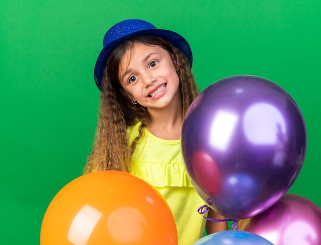 Smiling little caucasian girl with blue party hat holds helium balloons isolated on green wall with copy space