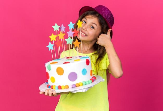 Sorridente bambina caucasica con viola party hat tenendo la torta di compleanno e sfogliando isolato sulla parete rosa con spazio copia