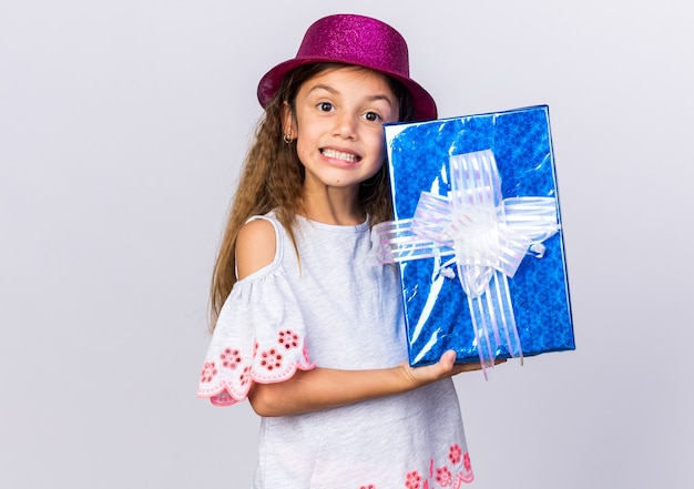Smiling little caucasian girl with purple party hat holding gift box isolated on white wall with copy space