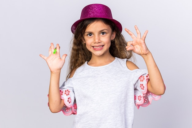 Smiling little caucasian girl with purple party hat holding party whistle and gesturing ok sign isolated on white wall with copy space