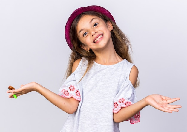Smiling little caucasian girl with purple party hat holding party whistle and keeping hand open isolated on white wall with copy space