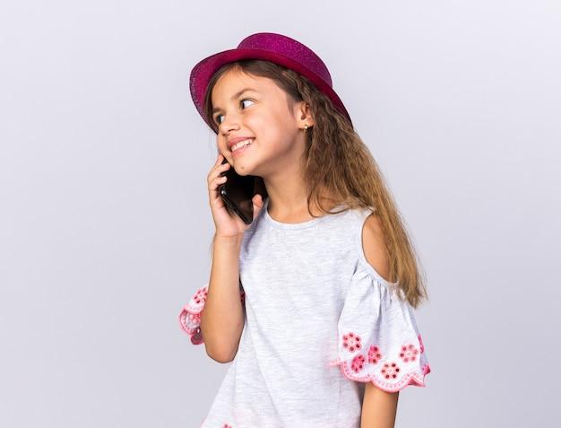 Piccola ragazza caucasica sorridente con il cappello viola del partito che esamina il lato che comunica sul telefono isolato sulla parete bianca con lo spazio della copia