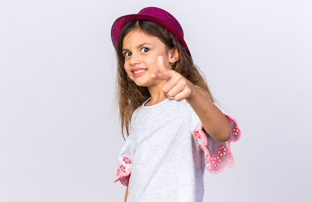 Smiling little caucasian girl with purple party hat pointing  isolated on white wall with copy space