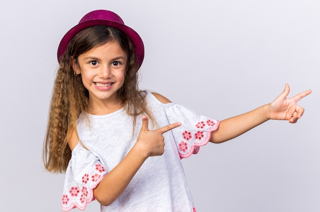 Smiling little caucasian girl with purple party hat pointing at side isolated on white wall with copy space