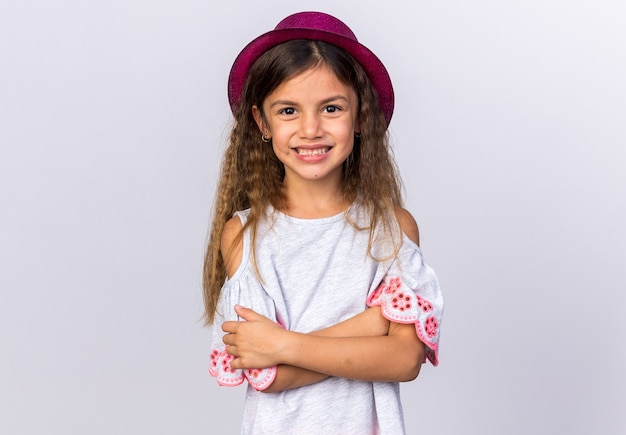 Smiling little caucasian girl with purple party hat standing with crossed arms isolated on white wall with copy space