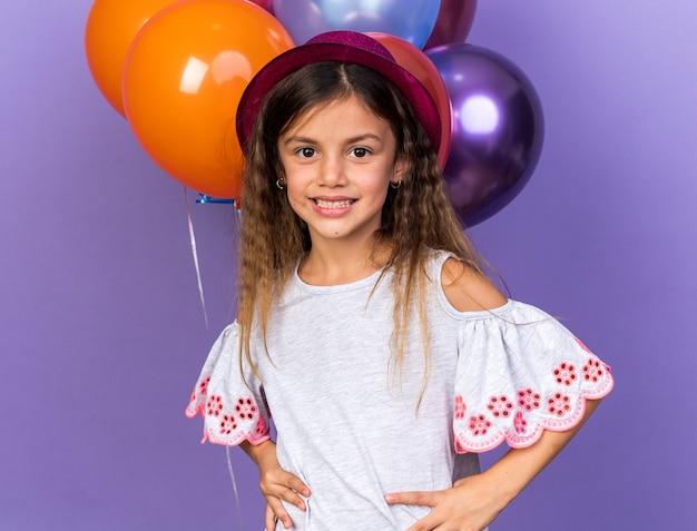 コピースペースと紫色の壁に分離されたヘリウム気球の前に立っている紫色のパーティーハットと笑顔の小さな白人の女の子