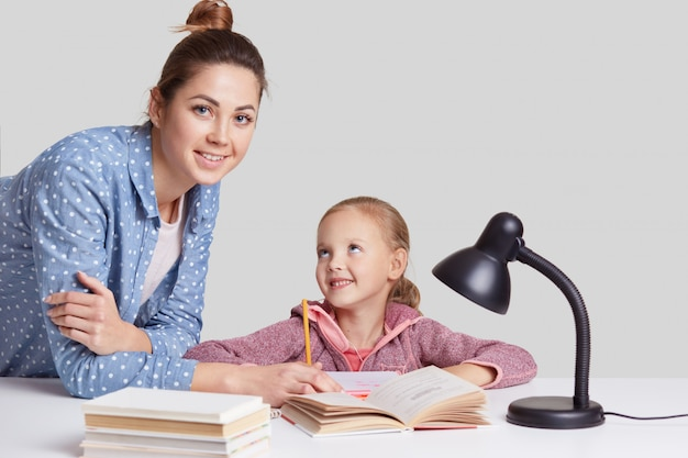 Smiling little charming girl sits at table, does homework task together with her mother, try to write composition, look joyfully, uses reading lamp for good vision, isolated on white wall