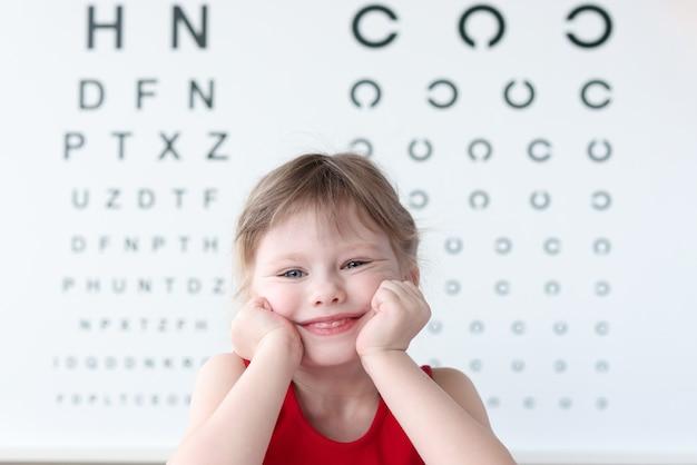 Улыбающийся маленький ребенок против таблицы проверки зрения в портрете медицинской клиники