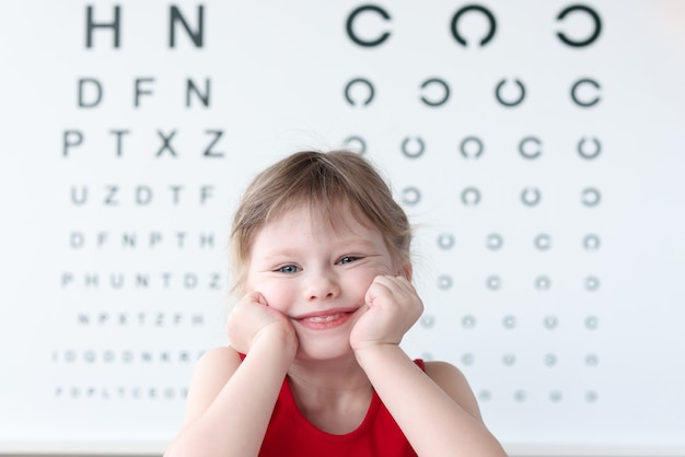 Smiling little child against vision test table in medical clinic portrait