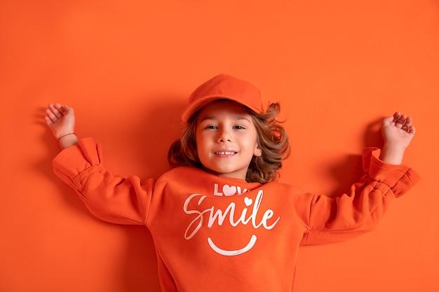 Улыбающаяся маленькая девочка 6-7 лет в кепке и модной одежде лежит на полу в студии на оранжевом фоне. копировать пространство
