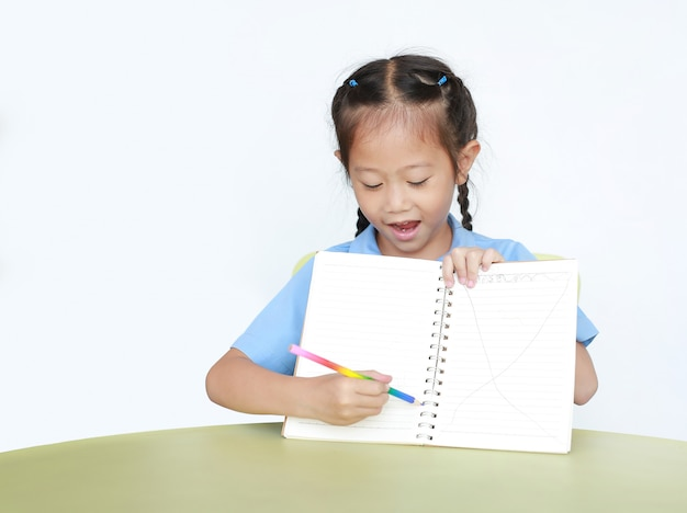 Smiling little child girl in school uniform show writing on blank notebook sitting at desk isolated .