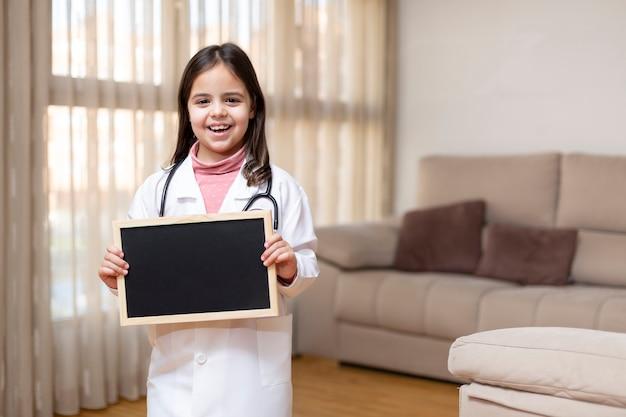 自宅で黒板を持っている医者の制服を着た小さな子供を笑顔