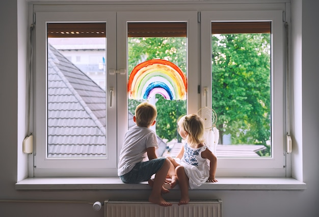 Smiling little children on background of painting rainbow on window