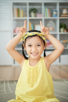 Smiling little chinese girl sitting at home and making cow horns gesture