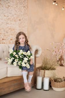 ジャスミンの花の花束と笑顔の小さな縮れ毛の少女は、居心地の良いリビングルームのソファに座っています。