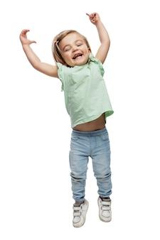 3歳の笑顔の少女がジャンプしています。ジーンズとtシャツの子供。活動と楽しい感情。白い背景で隔離。垂直。
