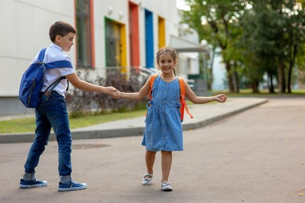 笑顔の少女と弟のバックパックと手をつなぐ