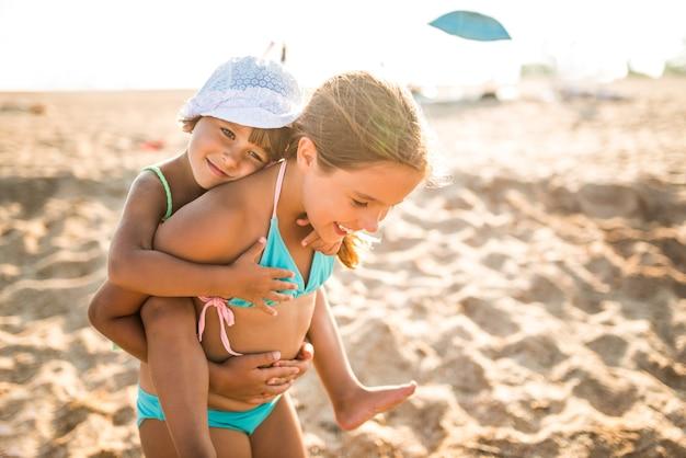 웃는 어린 소녀는 그녀의 뒤에 그녀의 작은 매력적인 여동생을 운반