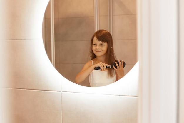 웃는 어린 소녀가 거울 앞 욕실에서 머리를 빗고, 반사된 모습을 보고, 집에서 옷을 입고, 미용 절차를 하는 것을 즐깁니다.