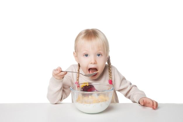 朝食を食べる小さな女の子の笑顔。白い背景で隔離