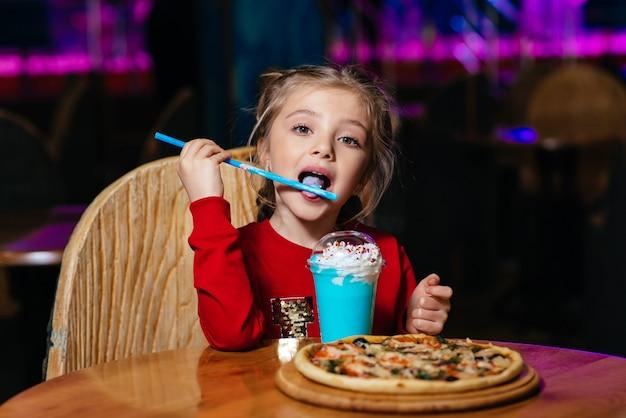 Улыбающаяся маленькая девочка ест мороженое Premium Фотографии