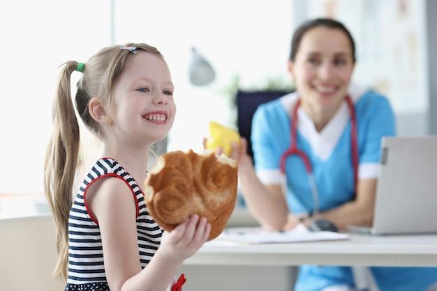 Улыбающаяся маленькая девочка ест булочку на фоне врача