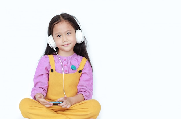 Smiling little girl enjoys listening to music with headphones isolated on white background with copy space.