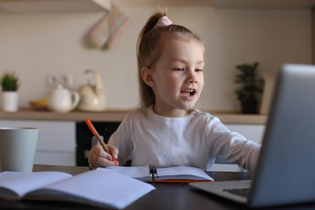 웃고 있는 어린 소녀가 집에서 노트북을 사용하여 온라인으로 손글씨 공부를 하고, 귀엽고 행복한 어린 아이가 인터넷 웹 수업이나 pc 수업을 받습니다.
