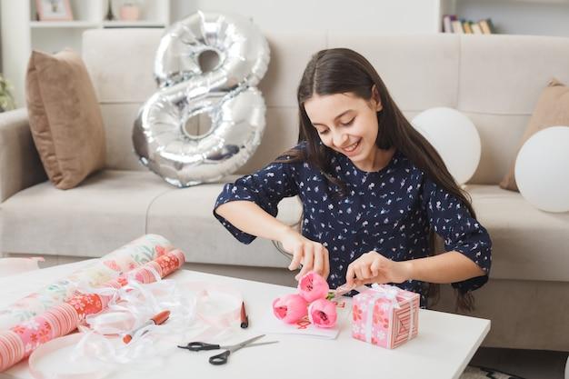 Bambina sorridente il giorno della donna felice tenendo e guardando i fiori seduta sul pavimento dietro il tavolino con regali in soggiorno
