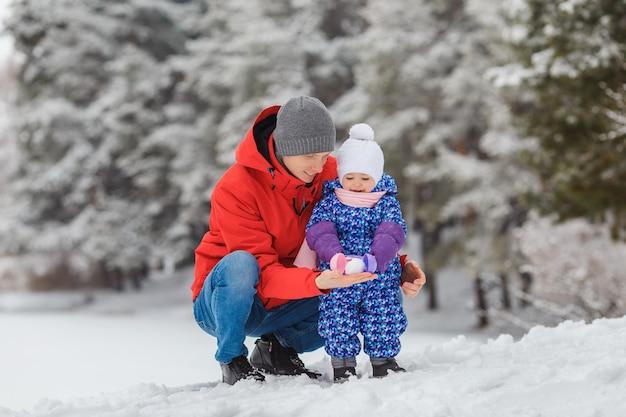 Улыбающаяся маленькая девочка с отцом в зимнем парке концепция счастливой семьи и детства