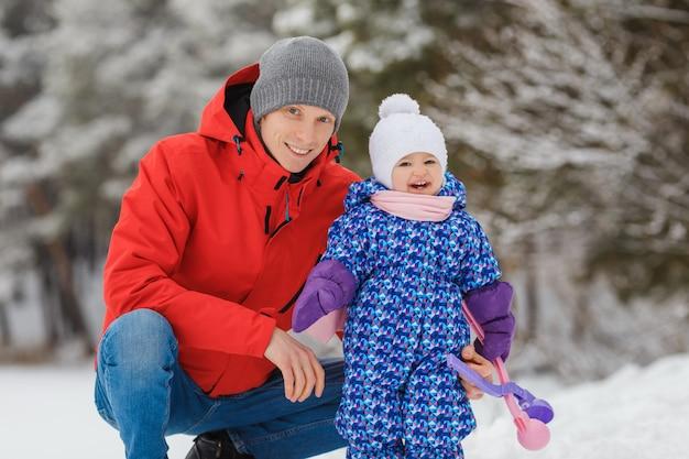 Улыбающаяся маленькая девочка веселится с отцом в зимнем парке милый ребенок с родителем играют в снежки