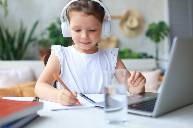 Smiling little girl in headphones handwrite study online using laptop at home, cute happy small child in earphones take internet web lesson or class on pc.