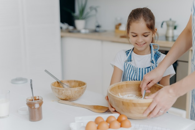 Smiling little girl helper holds big bowl, looks how mother is mixing eggs with flour