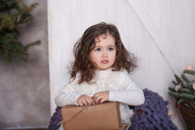 Улыбающаяся маленькая девочка с рождественским подарком, упакованная в крафт-бумагу
