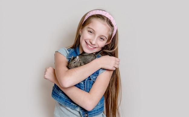 彼女の腕にdeguを保持している笑顔の少女