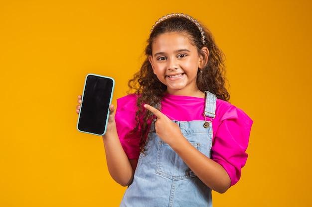 문자를 위한 여유 공간이 있는 흰색 화면이 있는 휴대폰을 들고 웃고 있는 어린 소녀.