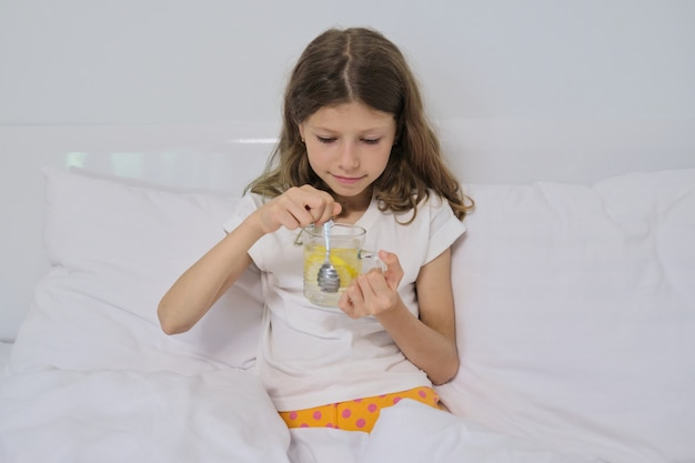 Smiling little girl holding a glass of natural homemade drink with lemon sitting in home white bed