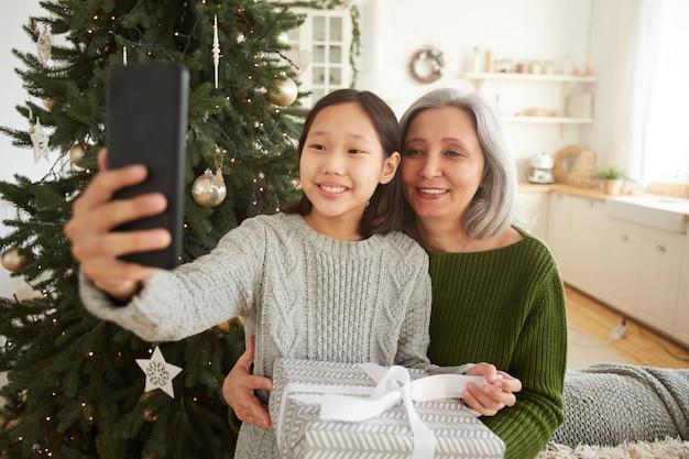 Улыбающаяся маленькая девочка держит свой мобильный телефон и фотографируется вместе с мамой возле елки
