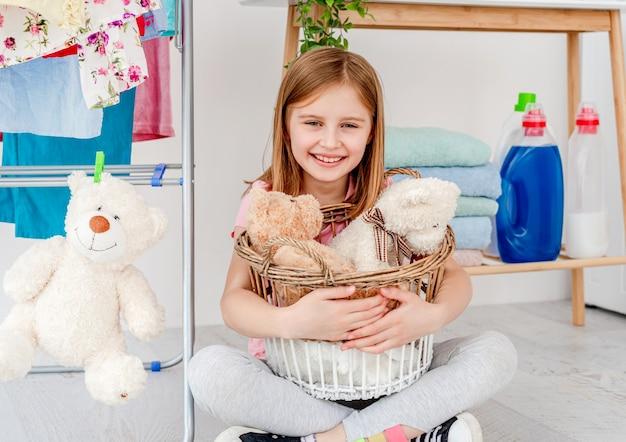Улыбающаяся маленькая девочка держит плюшевые игрушки в корзине для стирки, сидя на полу в ванной комнате