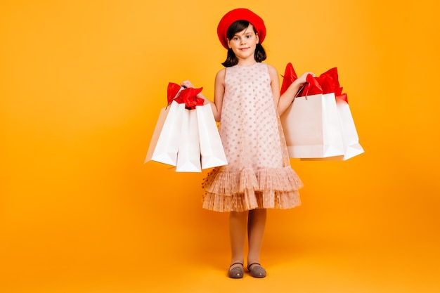 Smiling little girl holding shopping bags. cheerful kid in dress standing on yellow wall.
