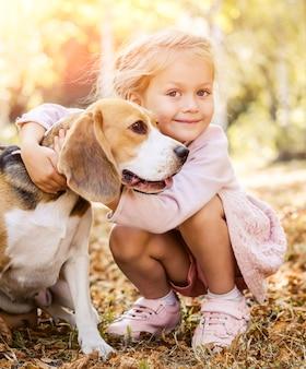 ビーグル犬を抱き締める小さな女の子の笑顔