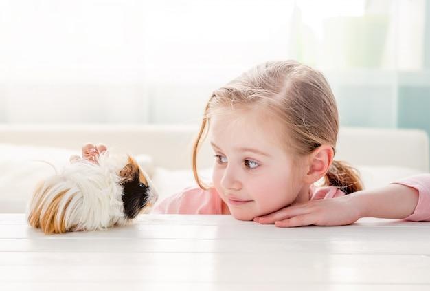 Улыбающаяся маленькая девочка обнимает морскую свинку